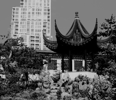 A black & white image of the Dr. Sun Yat-Sen Classical Chinese Garden in Vancouver, BC, Canada; showing the Chinese lake pavilion, with modern sky-scrapper building architecture in the background.